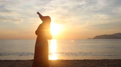 Silhouette of girl who admires scenery of sunrise above sea Stock Footage