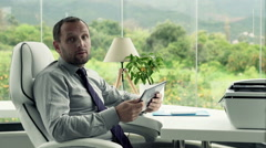 Friendly businessman with tablet computer talking good news to camera in office Stock Footage