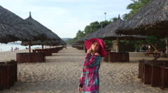 Girl in long dress poses on beach at umbrellas and comes Stock Footage