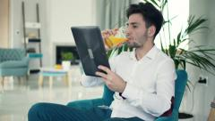 Stock Video Footage of Young man reading something on tablet computer and drinking beverage on armchair