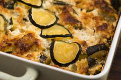 Casserole with cheese and zucchini in baking dish Stock Photos