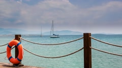 Wooden pier and orange life ring with anchored sailing yacht in the sea on the Stock Footage