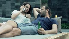 Couple talking on cellphone, drinking beer on on daybed in the evening HD Stock Footage