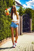 Stylish girl in sunglasses poses with longboard  front of green bush - stock photo