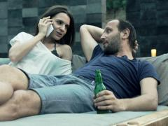 Couple talking on cellphone, drinking beer on on daybed in the evening NTSC Stock Footage