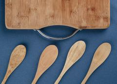Stock Photo of kitchen cutting board and a wooden spoon on a blue