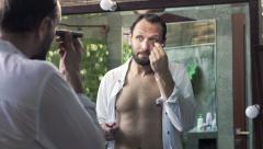 Handsome man applying concealer on his eyelid in bathroom HD Stock Footage