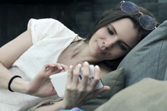 Woman watching photos on smartphone while lying on daybed NTSC Stock Footage
