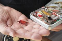 Artificial fishing flies in box and on hand Stock Photos