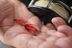 Artificial fishing flies in box and on hand - stock photo