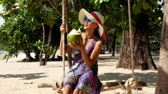 Asian Woman Sipping on Coconut on Tropical Beach - stock footage