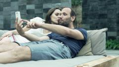 Happy couple taking selfie photo with cellphone lying on daybed Stock Footage