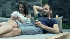 Young couple lying on daybed, woman using smartphone and man drinking beer Stock Footage
