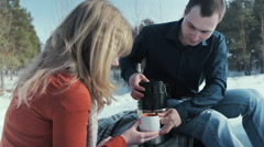 Young pair in wood. Man pours tea from a thermos Stock Footage