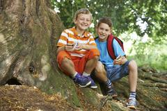 Two Boys Geocaching In Woodland - stock photo