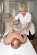 Masseuse working with a male client Providing a relaxing back massage Kuvituskuvat