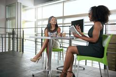 Two african american women discussing ideas using a tablet and computer - stock photo