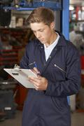 Apprentice Mechanic Working In Auto Repair Shop Stock Photos