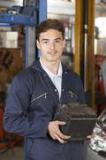 Apprentice Mechanic Holding Car Battery In Auto Repair Shop - stock photo