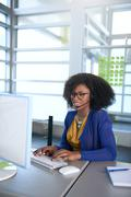 Portrait of a smiling customer service representative with an afro at the - stock photo
