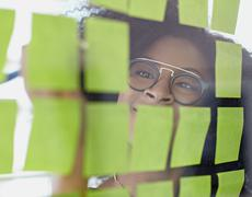 Portrait of a business woman with an afro behind sticky notes in bright glass - stock photo