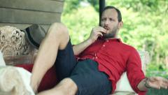 Sick man taking pill while lying on sofa on terrace Stock Footage
