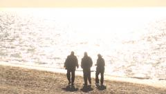 Three silhouette stroll along the promenade in the early morning. Slow motion. Stock Footage