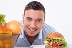 Handsome guy chooses between healthy and unhealthy food - stock photo