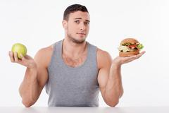 Stock Photo of Handsome man chooses between healthy and unhealthy food