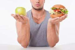 Stock Photo of Young fit guy is choosing between healthy and unhealthy food