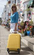 Holidaymaker with suitcase looking for B&B accommodation at a seaside town Stock Photos
