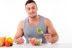 Handsome young man is eating healthy food - stock photo