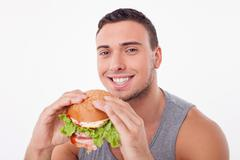 Stock Photo of Cheerful young sportsman is enjoying unhealthy food