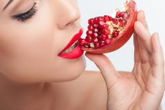 Attractive young woman is enjoying healthy fruit - stock photo
