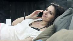 Pretty, young woman talking on cellphone while lying on daybed Stock Footage