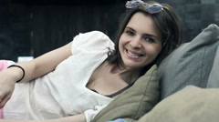 Portrait of pretty, happy woman lying on daybed Stock Footage