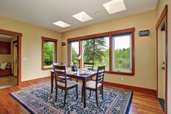 Simple dinning room with large windows. - stock photo