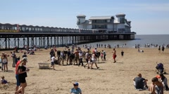 Weston-super-mare beach with donkies visitors tourists and the pier Stock Footage