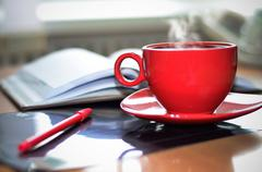 Red cup of hot coffee, notepad and pencil on the desktop in the office.  - stock photo