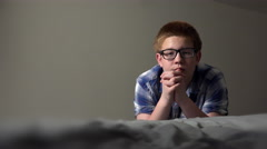 Young boy leaning against bed praying in dramatic light 4k - stock footage