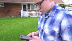 Young boy walking and texting in neighborhood 4k - stock footage
