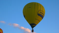 Flying hot air Balloons 35 - Follow yellow ballon in blue sky - early evening - stock footage