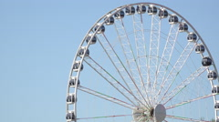 Ferris wheel rotates on blue sky background 4k Stock Footage