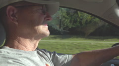 Elderly man driving car down highway in slow motion Stock Footage