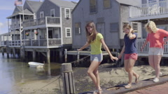 Girls Walk Single File Along Sea Wall On Nantucket Island (Slow Motion) Stock Footage