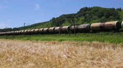 Train consisting of tanks for oil products moving along a wheat field - stock footage