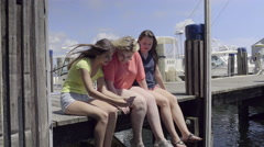 Friends Sit On A Dock And Take A Photo Together (4K) Stock Footage