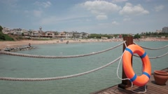 Wooden pier with orange life ring near the town's beach, 4k Stock Footage