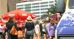 4K Crowd of people walk up to popular gourmet food trucks gathering urban city Stock Footage