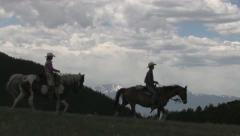 COWBOYS RIDING AND HERDING HORSES IN ROCKY MOUNTAINS Stock Footage